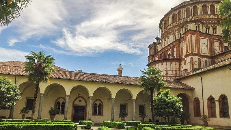 Il patio della basilica convento di Santa Maria delle Grazie con i suoi verdi cespugli e alcuni alberelli. Sulla destra si intravede la grande e altissima parte esterna della chiesa.