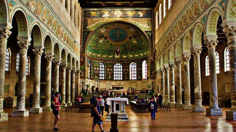 L'interno della basilica di sant'apollinare in classe con i suoi bellissimi mosaici laterali sopra i colonnati e il grande mosaico centrale sopra l'altare. I colori sono tutti colori chiari tra cui spicca il verde.