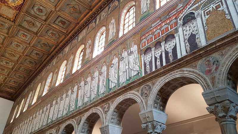 I mosaici laterali della basilica di sant'apollinare. Sono rappresentati dei discepoli vestiti in bianco ed è usato l'oro per lo sfondo. Sopra si intravede il soffitto cassettonato della chiesa.