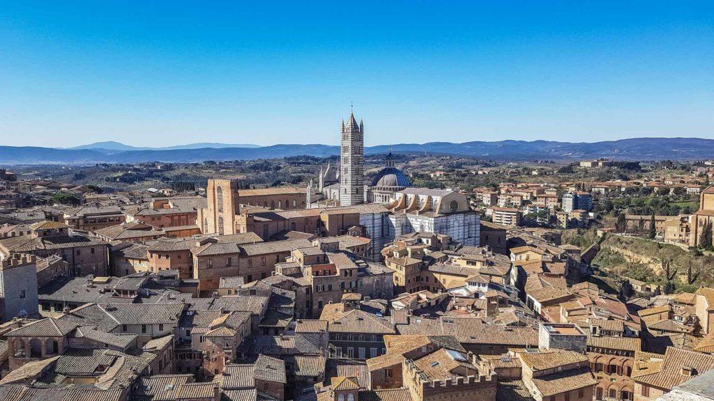 Una meravigliosa vista completa su tutta Siena con al centro della foto la bellissima cattedrale. Sullo sfondo colline e montagne. La città è sicuramente una delle mete da vedere in un giorno di vacanza!
