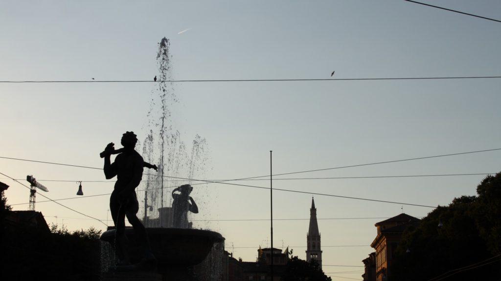 Un bellissimo primo piano su una delle fontane più belle di tutta Modena con le statue in risalto davanti e dietro lo spruzzo d'acqua. Sullo sfondo si vede il campanile a punta di una chiesa.