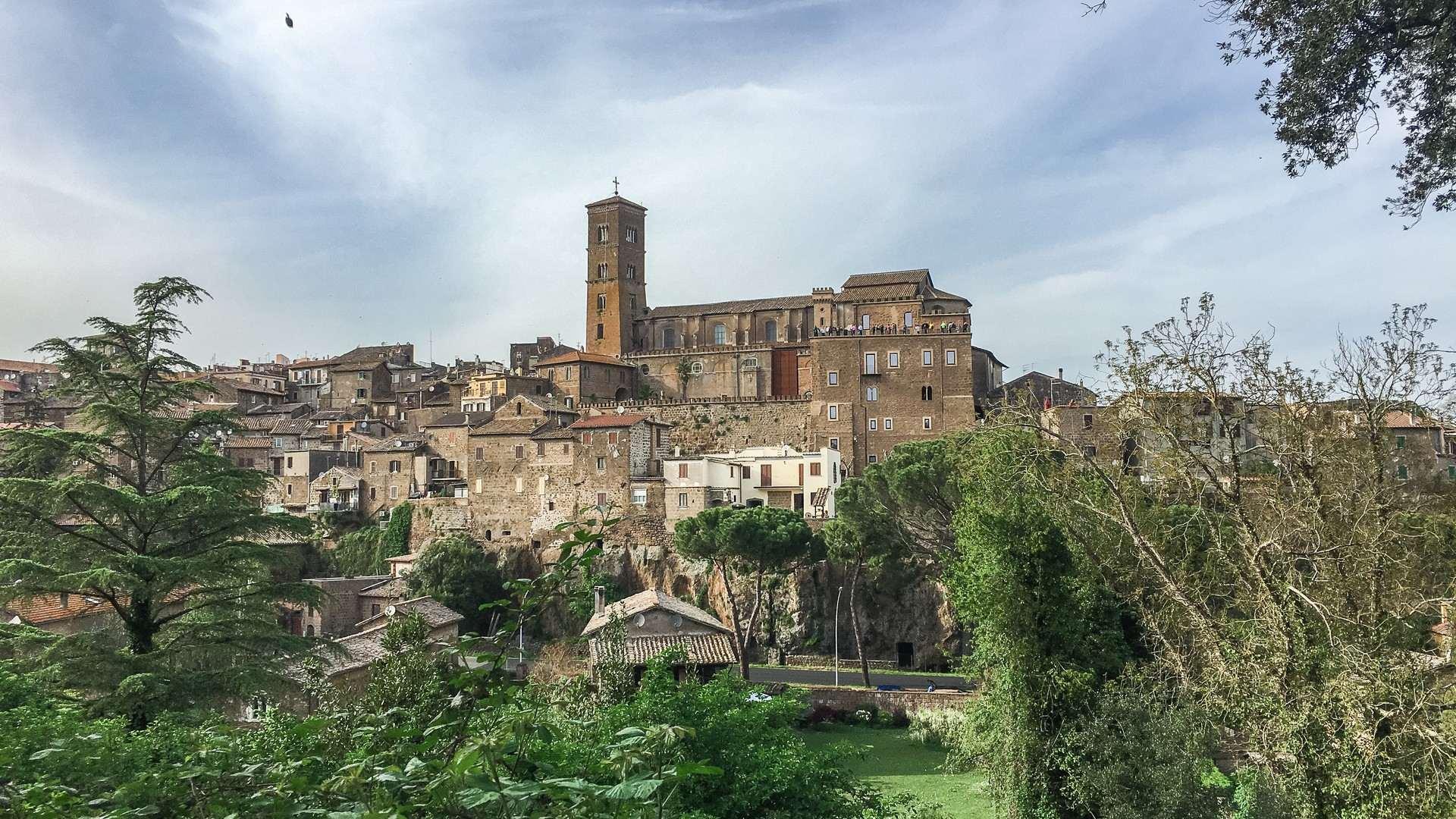 Il borgo di Sutri visto da lontano. Il paese si trova adagiato su uno sperone roccioso e spicca tra tutti gli edifici l'alto campanile della chiesa. In primo piano la verde vegetazione.