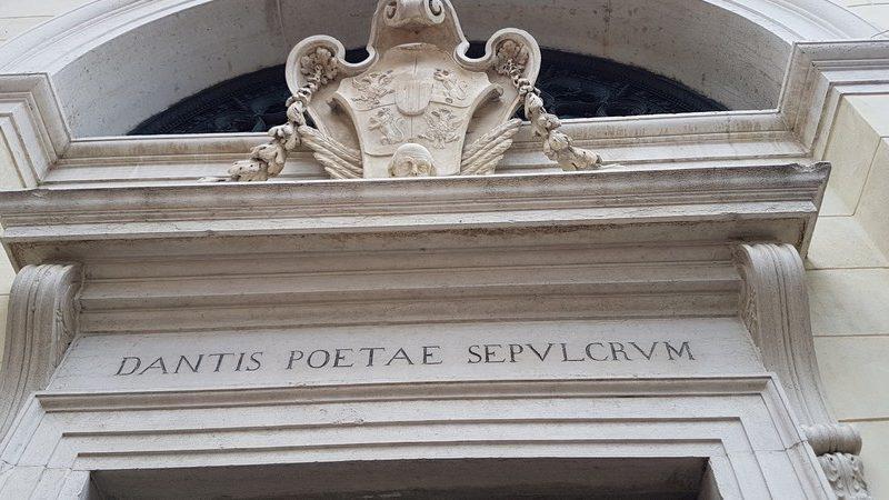 l'ingresso monumentale della tomba di dante a ravenna. Sopra la porta una grande scritta in latino annuncia al visitatore che qui è sepolto il grande poeta. Sopra il simobolo della città di ravenna.