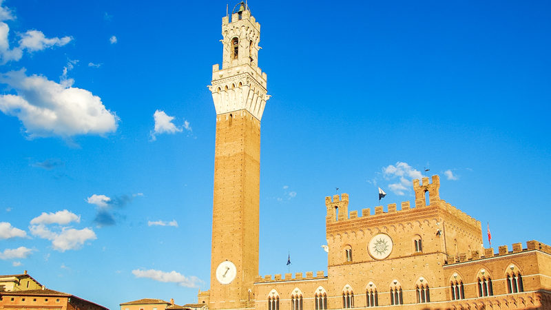 La torre del mangia a siena è altissima e sembra proprio entrare nel cielo azzurro. In basso presenta un grandissimo orologio mentre in alto sulla vetta la terrazza con la campana.