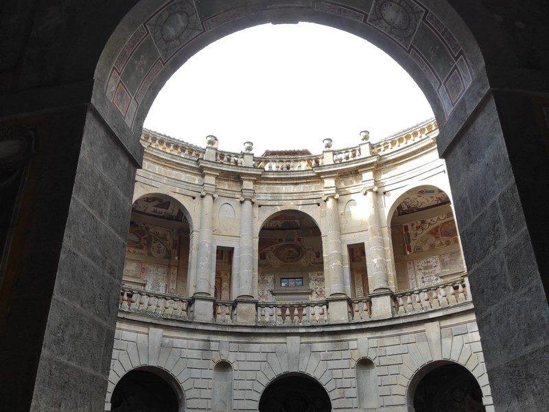 Il cortile esterno di Palazzo Farnese a Caprarola con le sue arcate elicoidali. In primo piano un grande arco di ingresso mentre sullo sfondo in alto si vedono gli affreschi del secondo piano.