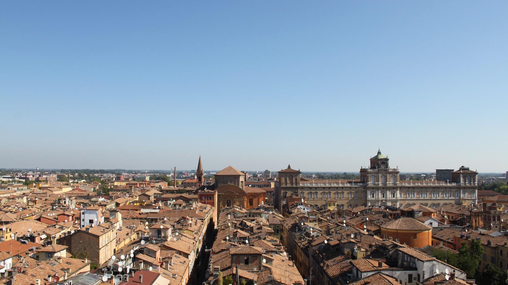 Una meravigliosa vista dall'alto di Modena su cui spicca in primo piano la sfarzosa facciata del palazzo ducale estense e il campanile di una chiesa.