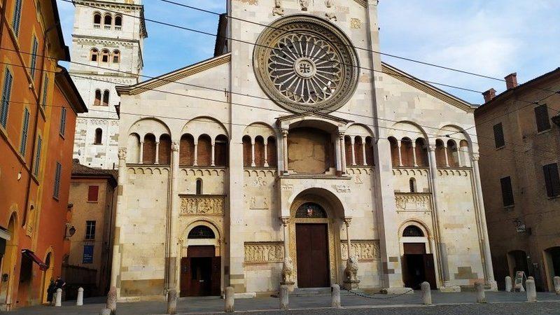 La facciata del Duomo di Modena con il suo enorme rosone centrale da cui penetra la luce. L'ingresso è composto da tre porte, la cui centrale è sorvegliata da due statue in marmo rappresentanti dei leoni.