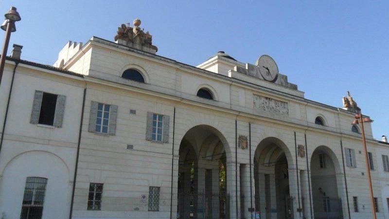 Un enorme edificio con tre arcate altissime sormontate da un grosso fregio in marmo. Sulla cima dell'edificio un grande orologio che mostra l'orario a tutti i passanti.