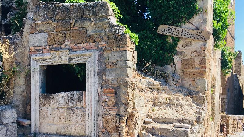Un rudere in massi di cui si vedono ancora interi l'ingresso arcato e la scalinata laterale. Sopra le scale un cartello che da il benvenuto a Celleno borgo fantasma.