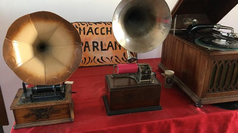 """Le macchine parlanti della mostra che viene fatta nel borgo fantasma di Celleno. Nella foto tre antichi grammofoni su cui veniva ascoltata la musica e dietro un cartello con scritto """"macchine parlanti""""."""