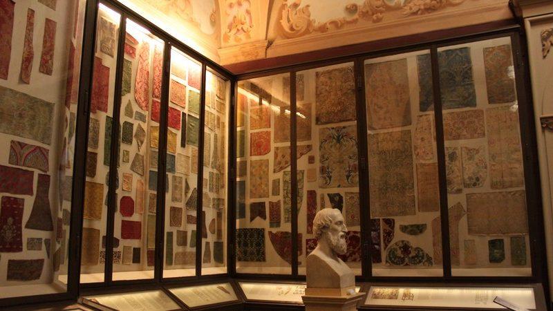 Una sala dei musei civici di Modena che contiene numerosi reperti dentro delle teche. In mezzo un busto in marmo.