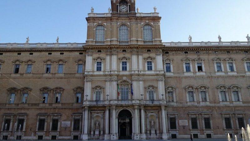 Il prestigiosissimo palazzo ducale di modena con la facciata a tre piani e con tante finestre. L'ingresso monumentale è composto da tre arcate di colonne con in mezzo due statue in marmo.