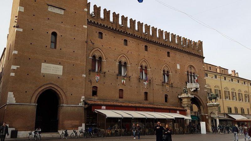 Un grandissimo edificio costruito da mattoni scuri e con grandi merlature sul tetto. L'entrata è monumentale con due colonne sormontate da statue di cavalieri a cavallo.