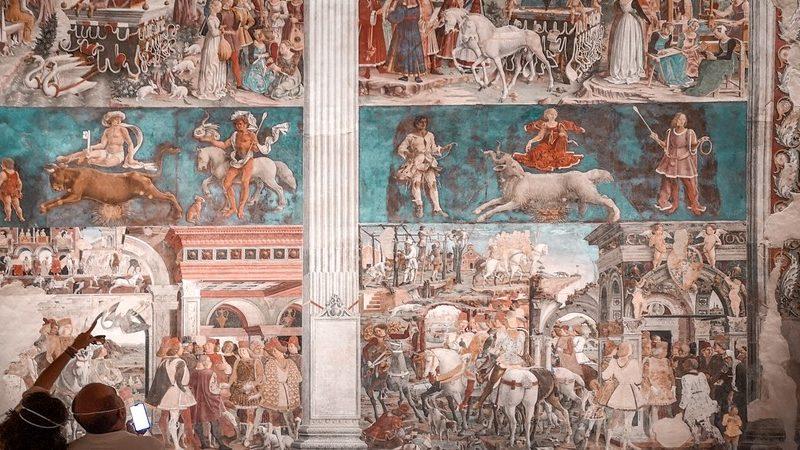 I bellissimi affreschi delle mura della sala all'interno del palazzo schifanoia. Gli affreschi rappresentano scene di guerra e in colori molto caldi come azzurro e rosso.