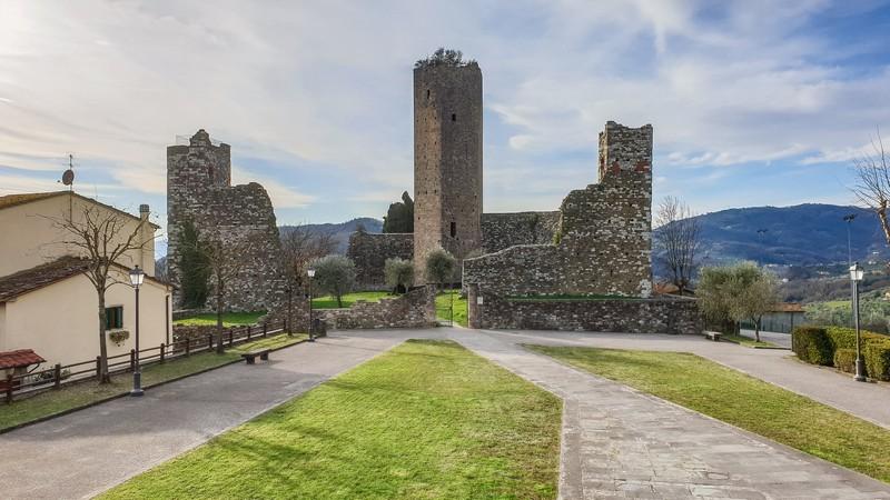 Una vialetto costernato da piccoli prati che porta alla bellissima Rocca Nuova di Serravalle Pistoiese. Al centro l'alta torre contornata dai resti delle mura difensive. Sulla destra i verdi colli della Valdinievole.