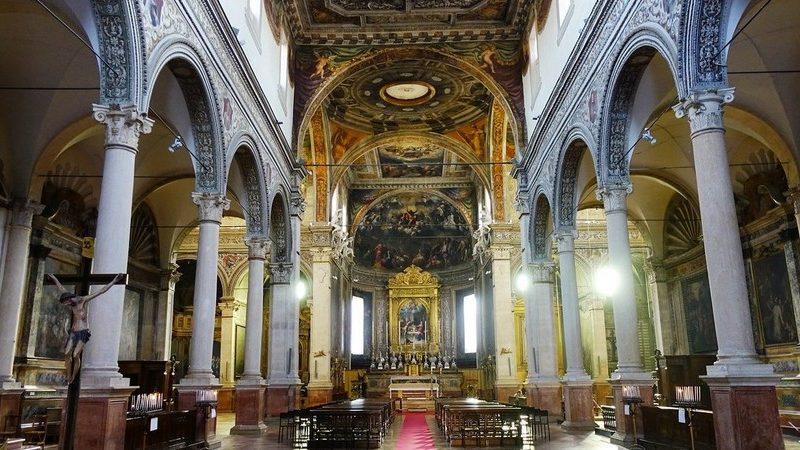 Il bellissimo interno della chiesa di santa maria in vado a ferrara. Si notano gli affreschi sul soffitto e in primo piano i corridoi laterali divisi da colonnati altissimi.