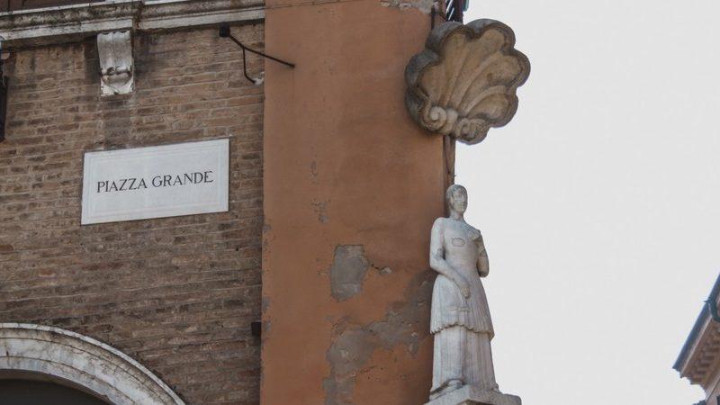 Un angolo di Modena dove è possibile vedere affisso al muro la targa con scritto Piazza Grande e accanto la piccola statua della bonissima sormontata da una grande conchiglia di marmo.