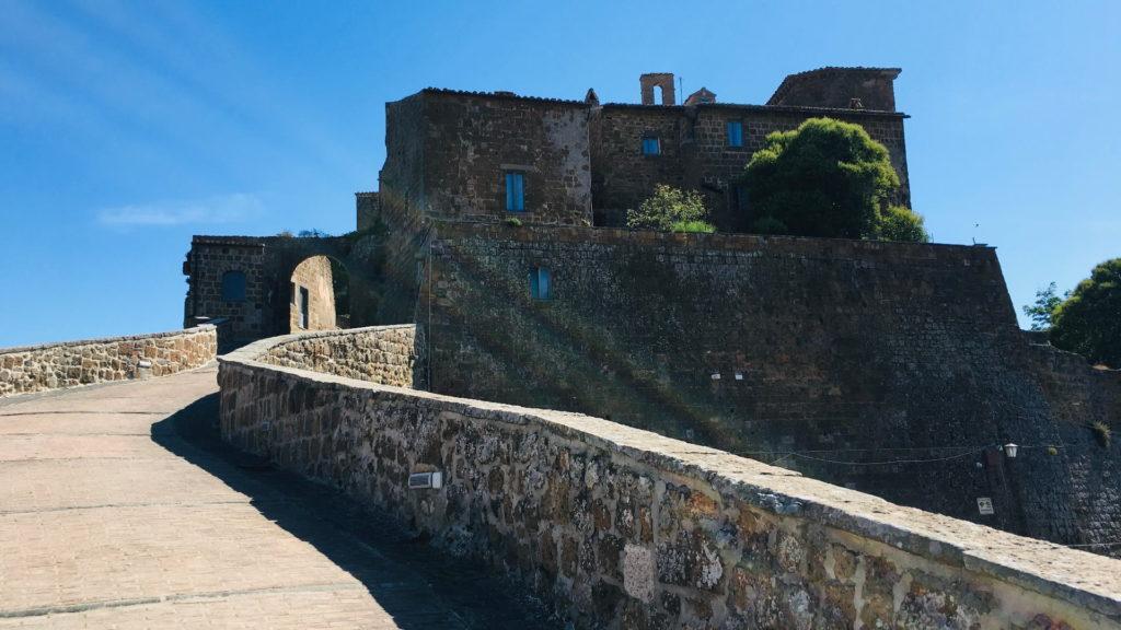 Una passeggiata che accompagna il turista all'entrata del borgo fantasma di Celleno. Si vede sullo sfondo l'arco dell'entrata al borgo e accanto spiccano le case in mattoni.