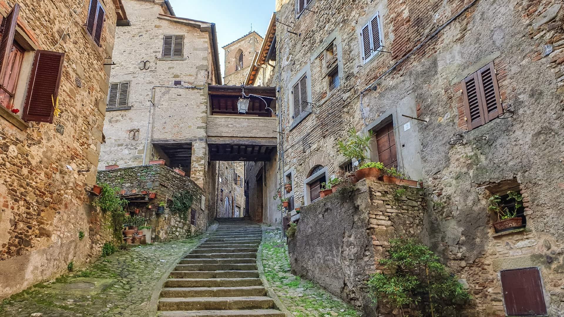 Una via scalinata circondata da case in pietra, che porta alla torre dell'orologio di Anghiari il paese della battaglia. In fondo c'è un passaggio sopraelevato coperto che collega due abitazioni.