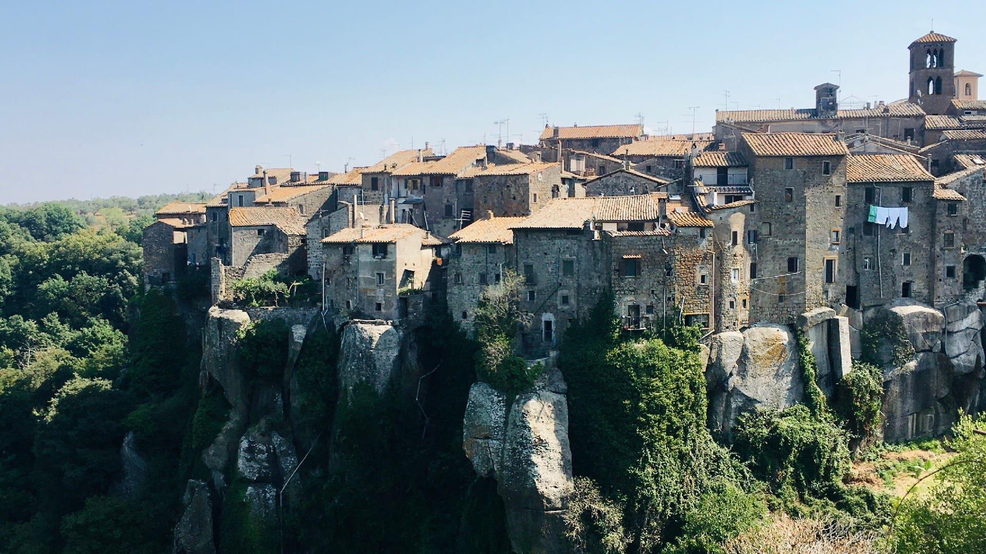 Il grande sperone tufaceo su cui sorge il borgo di Vitorchiano (Viterbo). Il borgo è costituito da tante casette in pietra tufacea. Lo sperone è circondato da alberi e verde vegetazione.