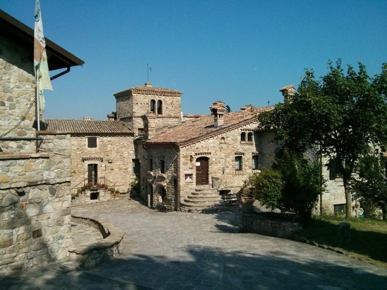 Un angolo di pace e silenzio di Votigno di Canossa con tutte le sue abitazioni costruite in pietra. Sulla destra un piccolo giardino con un grande albero verde.