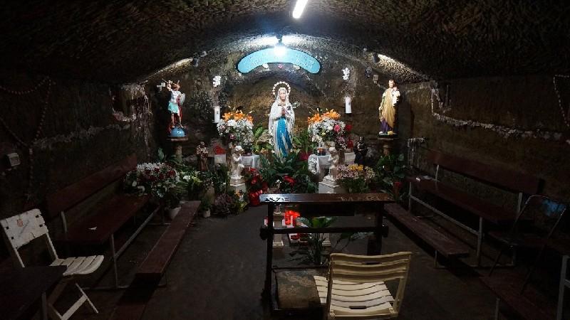 La Grotta delle Apparizioni di Marta lago di Bolsena. La grotta è molto piccola ma ha delle sedie su cui sedersi, diversi fiori colorati e una grande statua centrale della Madonna.