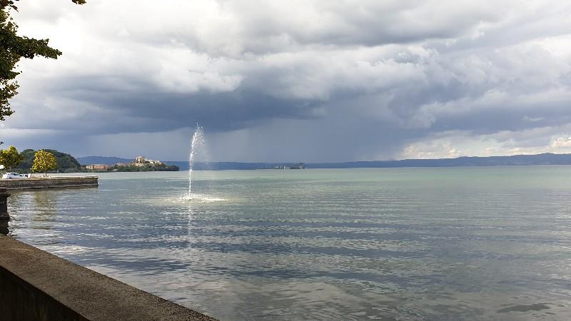 L'acqua azzurra del lago di Bolsena vista dal lungolago di Marta. Si intravede sullo sfondo il borgo di Capodimonte e in primo piano una fontana spruzzare acqua nel mezzo del lago.