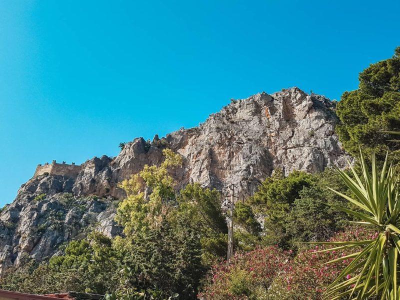 Un altissima rupe rocciosa contornata da fitta verde vegetazione. In cima a sinistra si intravede parte dell'antica fortificazione della Rocca di Cefalù.