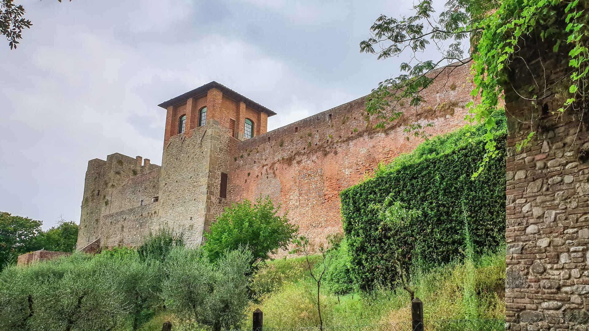 Le alte mura in pietra della Fortezza del Cerruglio di Montecarlo di Lucca. In primo piano si vedono i due torrioni quadrati con sotto alcuni ulivi e cespugli verdi.