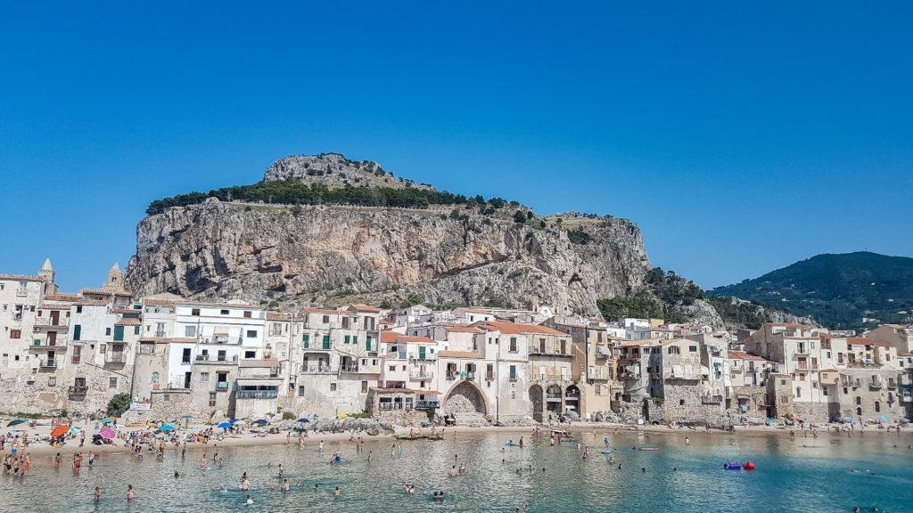 Una vista completa sul borgo di Cefalù con in primo piano le case bianche e le spiagge piene di persone e l'acqua cristallina. In alto invece l'altopiano roccioso su cui sorge la rocca di Cefalù.