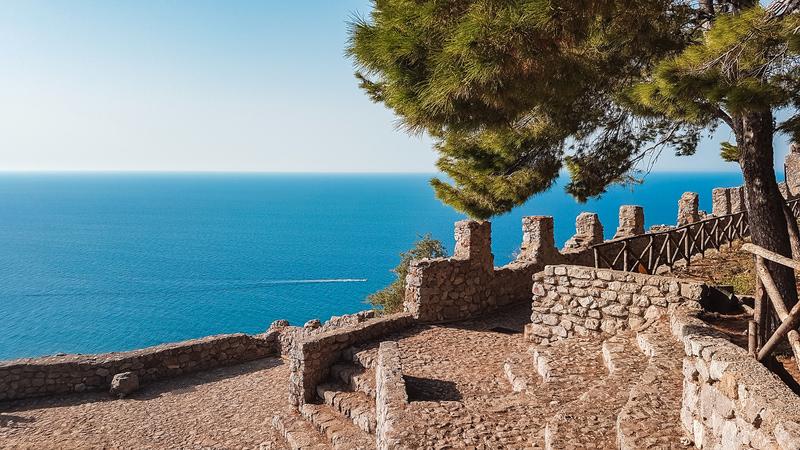 Il camminamento acciottolato che porta sulla cima della Rocca di Cefalù. Sullo sfondo il bellissimo mare azzurro mentre in primo piano ci sono le mura merlate del 15° secolo d.C.
