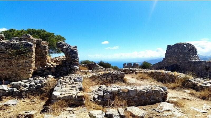 I ruderi in pietra di ciò che rimane dell'antico castello di Cefalù. Sullo sfondo a sinistra un grande albero verde si staglia nel mezzo dei resti e del cielo azzurro.