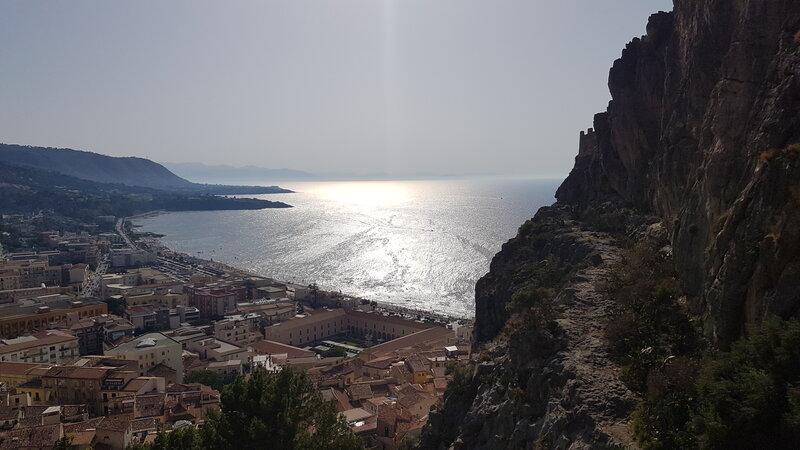 Una vista parziale dall'alto sulle case di Cefalù e l'acqua cristallina del mare illuminata dal sole. Sulla destra un sentiero ricoperto di vegetazione e sassi che porta alla Rocca di Cefalù.