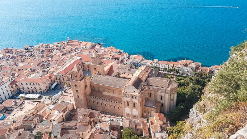 Una vista meravigliosa su tutto il borgo con in primo piano il Duomo di Cefalù e la grande piazza antistante. Più avanti si vede l'acqua blu del mare con una piccola barca che si muove verso destra.