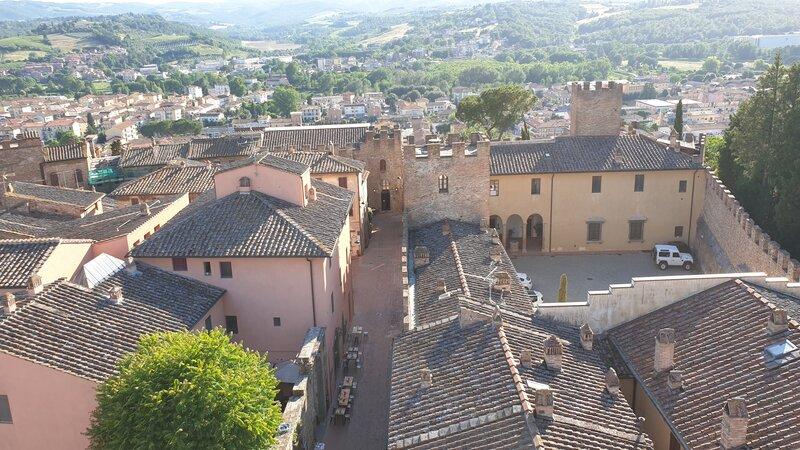 La vista sulla via principale di Certaldo Alto e sulla valle. In primo piano ci sono le antiche case torri merlate mentre sullo sfondo il verde della Val d'Elsa e le case del borgo nuovo di Certaldo.