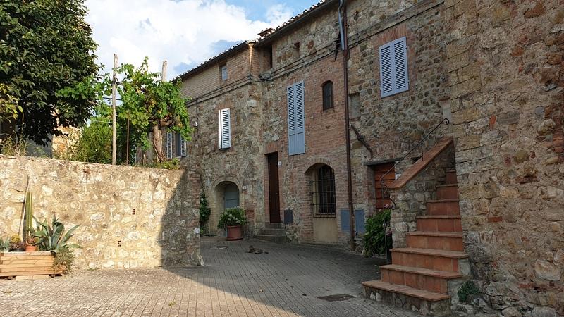 Una contrada del piccolo paese di Murlo Siena con le sue casette tipiche in pietra. Sullo sfondo si vede un gatto all'ombra nel mezzo dei fiori che abbelliscono gli ingressi delle abitazioni.