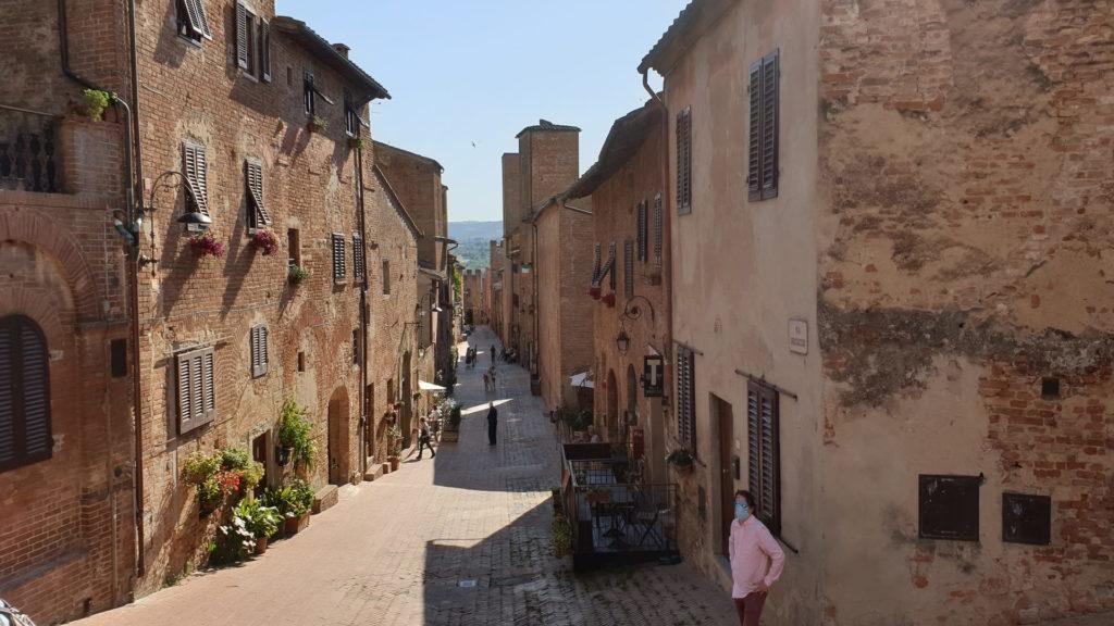 La via principale di Certaldo Alta, via Giovanni Boccaccio, con le sue abitazioni in mattoni decorate da piante verdi agli ingressi e fiori colorati sulle finistre.