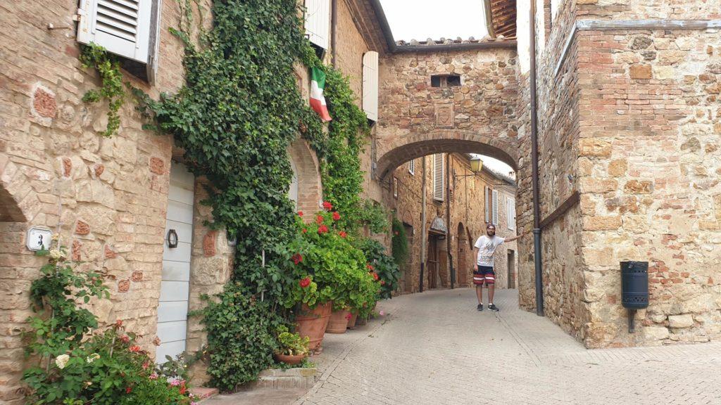 Un primo piano su via delle carceri di Murlo. Davanti ci sono le piante verdi rampicanti e i fiori rossi che abbelliscono l'abitazione. Sullo sfondo invece un arco con il simbolo di Murlo Siena.