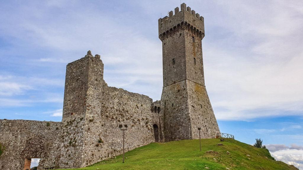 L'alto mastio dell'antico castello di Radicofani che si staglia su un cielo azzurro sereno e si appoggia su un colle verde. Accanto i resti ancora in piedi delle mura difensive.
