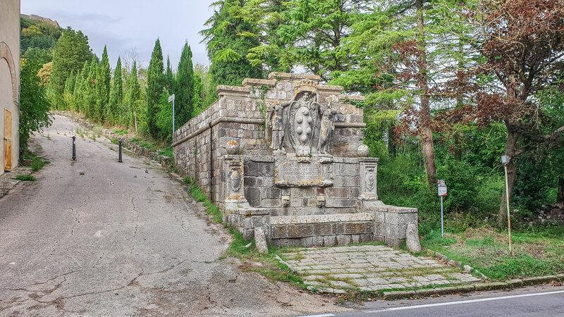 Un antica fontana in pietra nel mezzo di un viale alberato che porta fino al borgo di Radicofani e alla Rocca di Radicofani. Al centro della fontana il grandissimo simbolo della famiglia Medici.