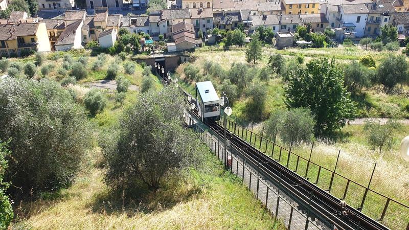 La funicolare di Certaldo che va presa per arrivare fino al borgo storico in alto sulla collina. In basso si intravedono le case di Certaldo e in primo piano le rotaie su cui viaggia il mezzo.