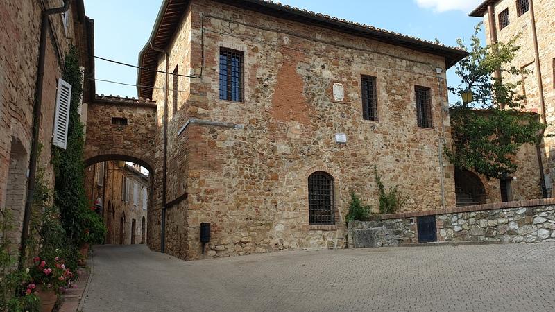 Una piccola piazza con un edificio in pietre miste e sullo sfondo un arco che collega l'edificio ad un altro. Sulla sinistra fiori colorati abbelliscono l'entrate delle abitazioni.