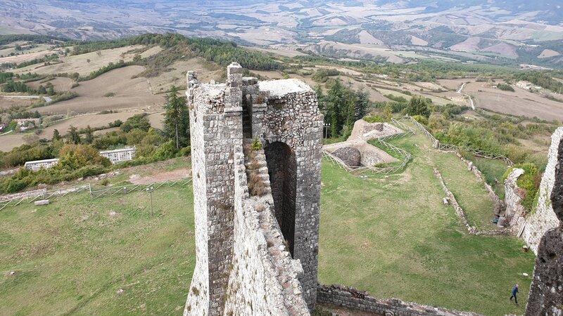 La vista su tutta la Val d'Orcia dalla cima della Rocca di Radicofani. In primo piano un bastione medievale che componeva le fortificazioni del castello, oggi solo ruderi (visibili in basso).