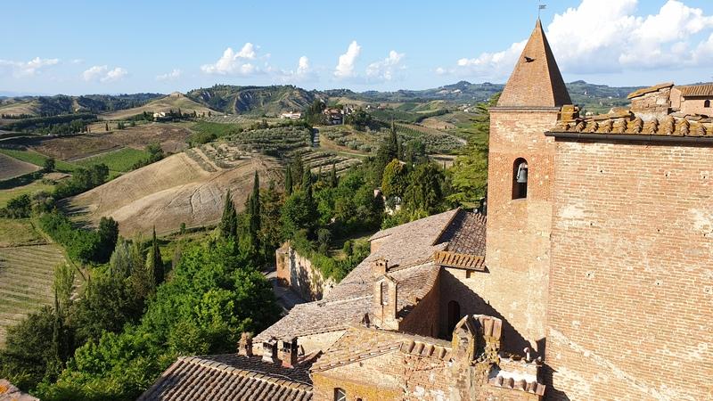 La vista su parte del borgo e sulle colline verdi della Val d'Elsa. A destra si vede il campanile della chiesa del borgo e i mattoni delle abitazioni. A sinistra il verde degli alberi e delle colline.