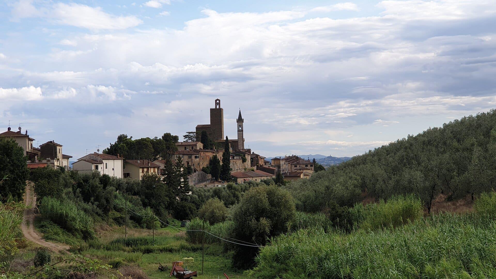 Il bellissimo paese vinci visto da lontano da una collinetta verde. Si può notare due edifici che si stagliano verso il cielo azzurro, la torre del castello e il campanile della chiesa.