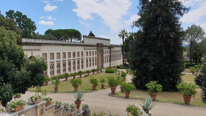 La grandissima limonaia nei giardini esterni della villa. E' una struttura piena di finestre e con intorno tantissimi vasi con piante e altissimi alberi verdi.