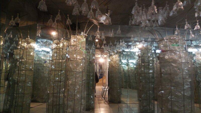 Un enorme stanza del museo del cristallo dove sono contenuti contenitori pieni di pezzi di cristallo lavorati. Sul soffitto sono appesi a capo in giù tantissimi bicchieri di cristallo.