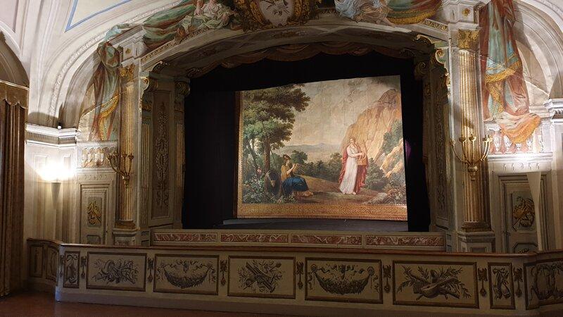 Il piccolo teatro custodito all'interno di una delle sale della villa medicea poggio a caiano. Si vedono le grandi decorazioni che contornano il palcoscenico e sul frontespizio una scena di una rappresentazione.