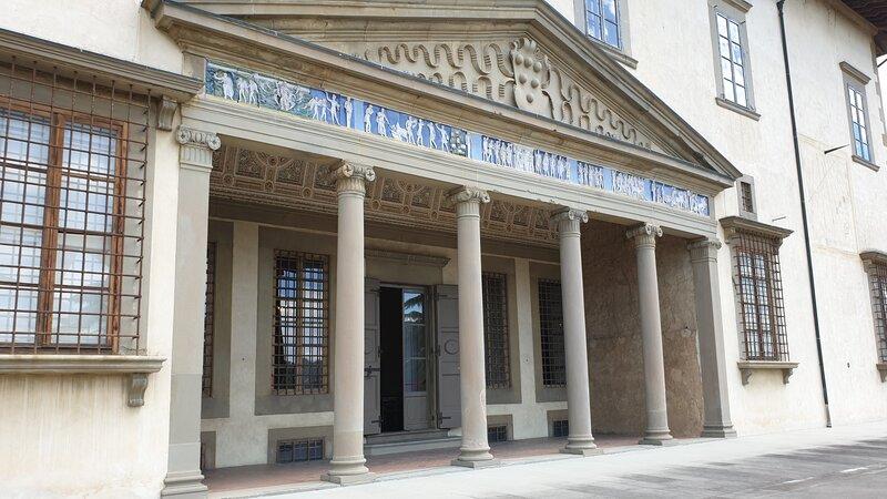 Il terrazzino della villa medicea di poggio a caiano con i suoi fregi di colore blu sopra sei colonne che tengono il tutto. In cima si vede il grande simbolo della famiglia dei medici.