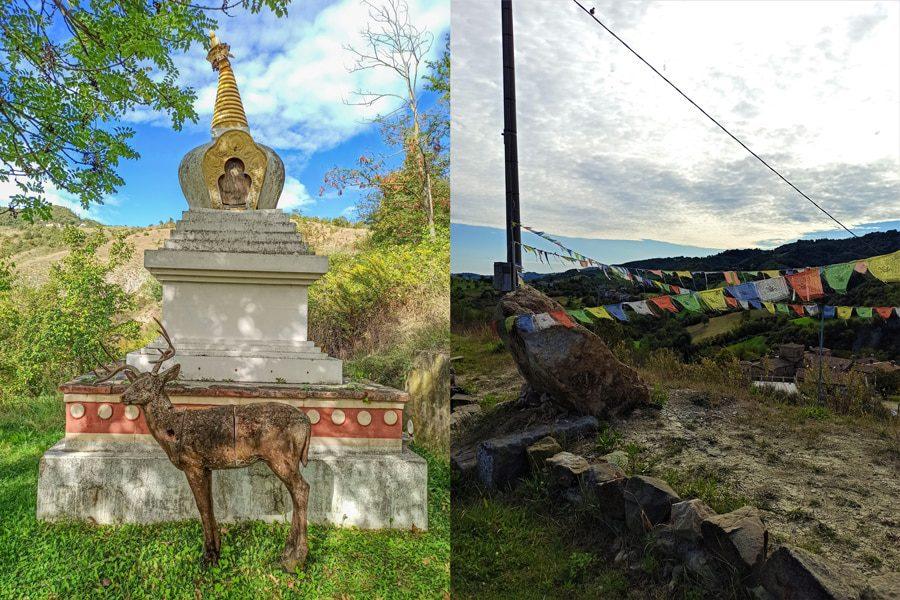 Sulla sinistra una statua con un cervo nel mezzo del verde della vegetazione. A destra invece le bandiere colorate che abbelliscono il paese di Votigno di Canossa.